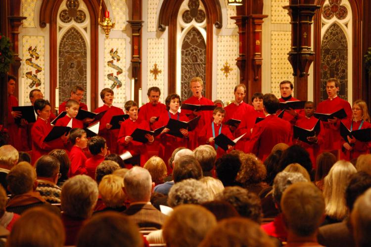 Group performing in the church with red robes.
