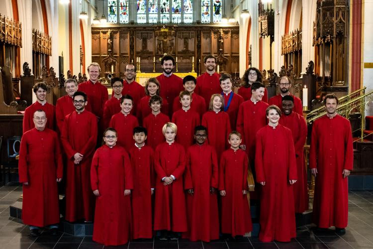 Choir of boys and men in red cassocks standing in Cathedral