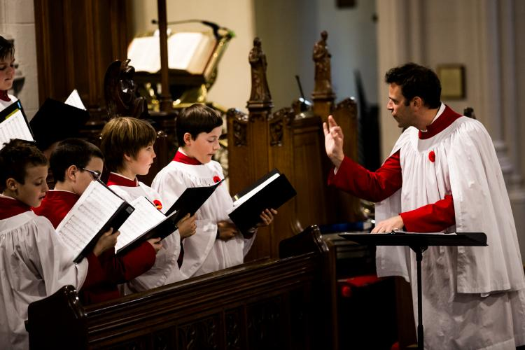 Director conducting four boy choristers during a church service