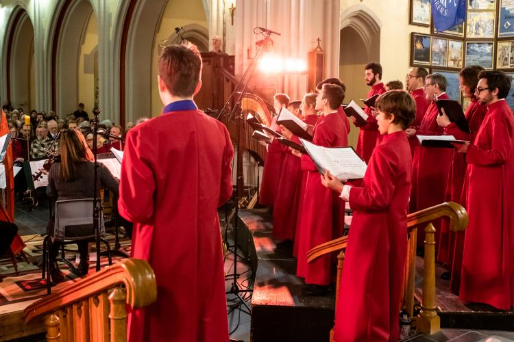 View of choristers from the back as they perform in Cathedral to full audience