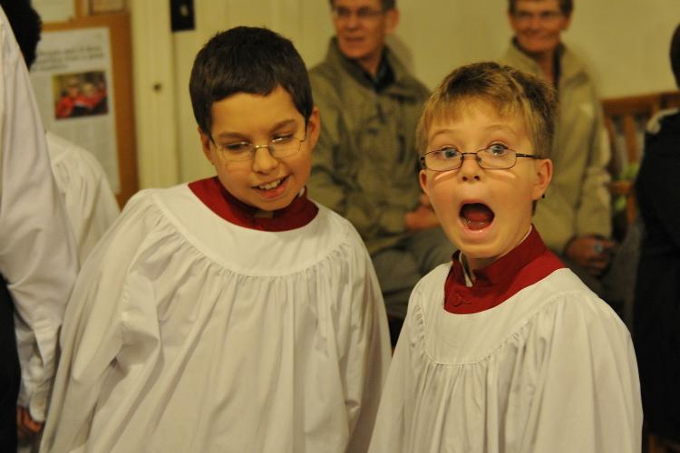 Two young choristers in service cassocks making funny faces