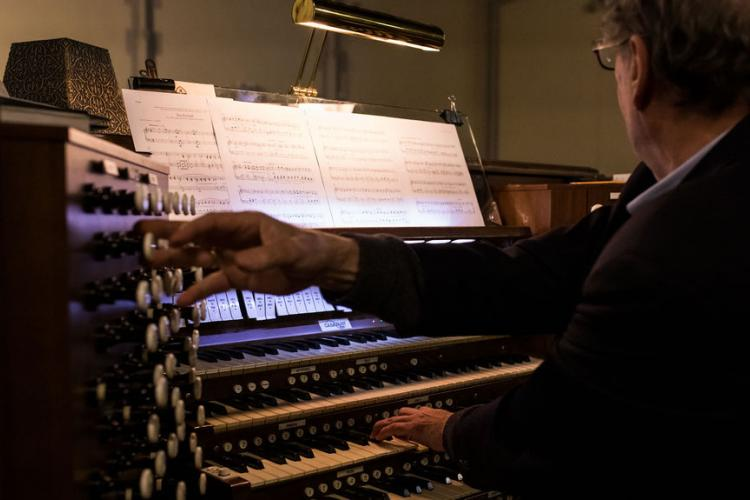 Paul Halley playing organ - one hand on keyboard, one hand pulling stops