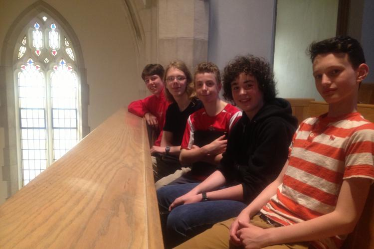Young Men sitting in a row in a church balcony pew