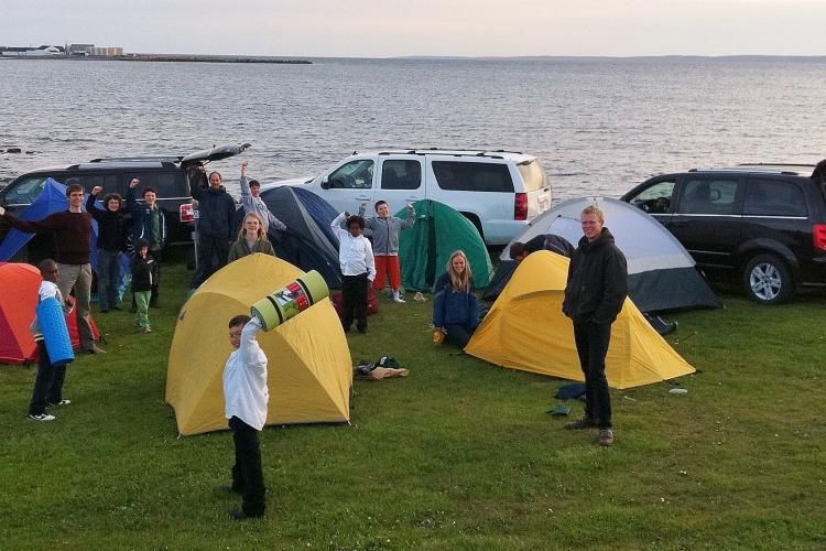 Informal photo of choir members standing with camping tents and vans at seaside during tour