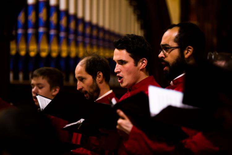 Four men of the choir singing during concert, organ pipes in background