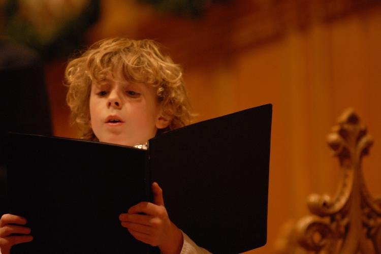 Young chorister singing and looking at music in black music folder