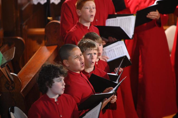 Boy choristers in red robes in a row, singing during concert