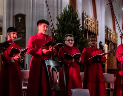 Six boy choristers singing during a performance (2019).