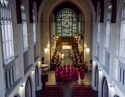 Photo taken from high up in Cathedral clerestory windows, looking down the nave towards high altar and stained glass window, with the choir in red robes in the crossing.