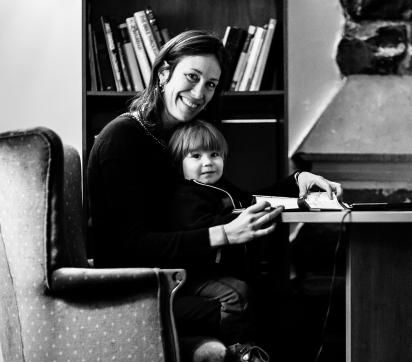 Vanessa Halley in chair with young son and deskwork on her lap
